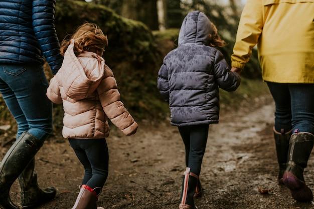 Madre che cammina con le sue figlie nella vista posteriore della foresta