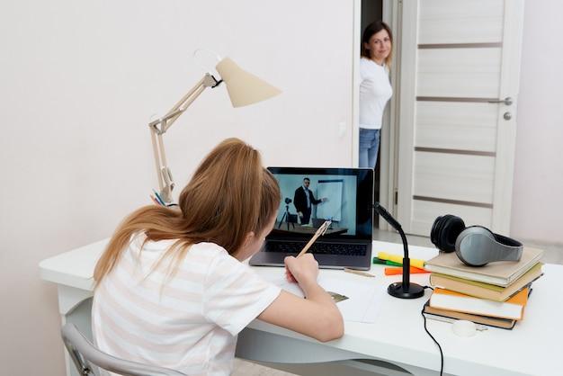 Generi guardare sua figlia che fa i compiti sul computer portatile a casa