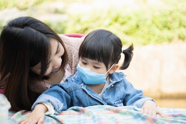 La madre indossa una maschera per i suoi figli, protegge il coronavirus covid-19 nel bar