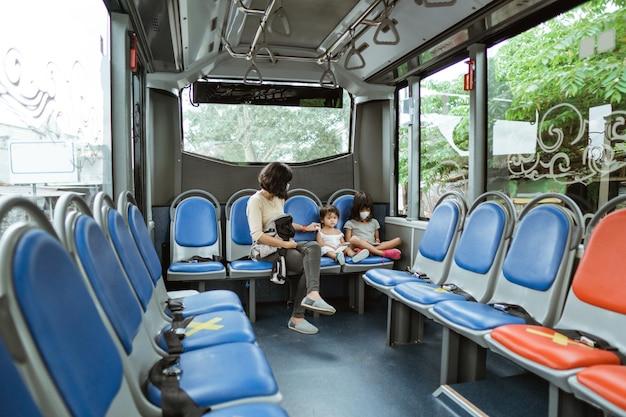 Una madre che indossa una maschera e le sue due figlie siedono sul sedile posteriore dell'autobus lungo la strada