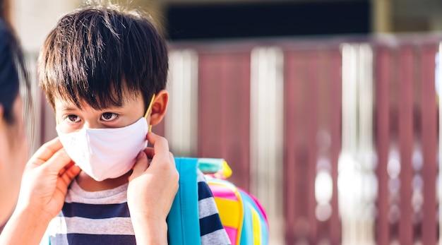 La madre che indossa la maschera per il figlio del piccolo ragazzo asiatico per il coronavirus è pronta a tornare a scuola dopo il covid19