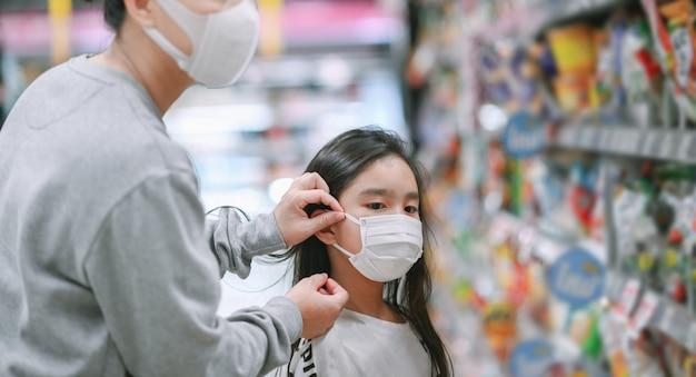 La madre che indossa una maschera protettiva mette una maschera su una figlia in un supermercato