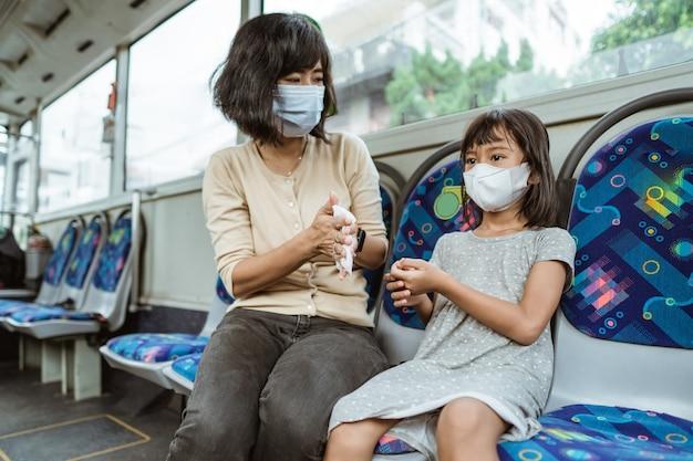 Una madre indossa una maschera e sua figlia usa un fazzoletto per lavarsi le mani mentre è seduta sull'autobus
