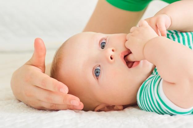 Madre con la madre del primo piano del bambino che bacia il suo bambino sulla guancia sul letto bianco
