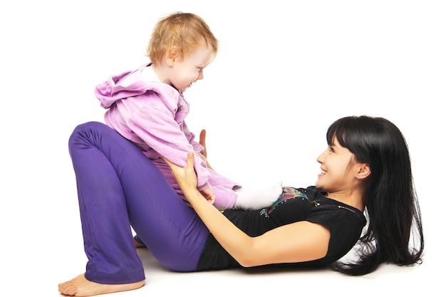 Madre con il bambino che fa esercizi su bianco