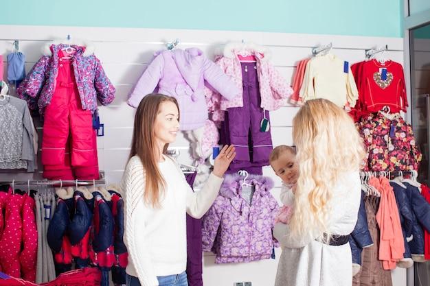 La mamma con il bambino visita il negozio di abbigliamento con abbigliamento invernale