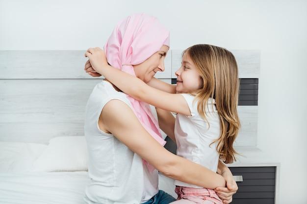 La madre malata di cancro indossa un velo rosa che abbraccia felicemente la sua bellissima figlia bionda. sono entrambi seduti sul letto con uno sfondo bianco