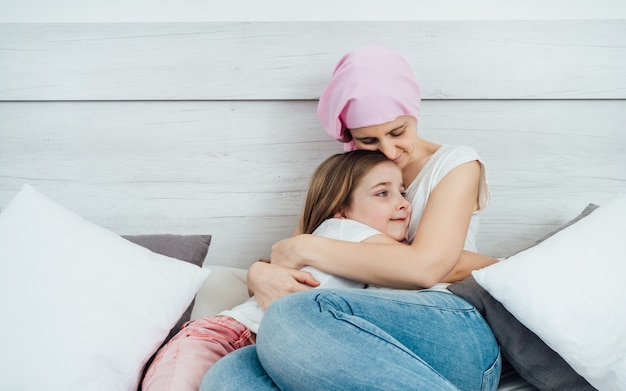 Una madre malata di cancro indossa un velo rosa e abbraccia teneramente la sua bellissima figlia bionda. sono entrambi seduti sul letto con uno sfondo bianco