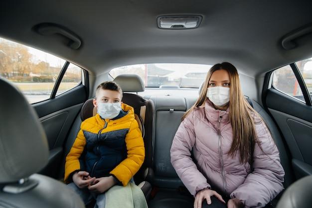 Una madre con un bambino sul sedile posteriore di un'auto in maschera che va in ospedale. epidemia, quarantena.