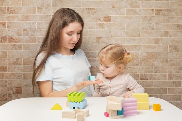 Madre con un bambino che gioca con i blocchi di legno a casa
