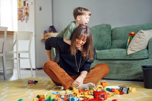 Madre con bambini che si abbracciano, si divertono, si ride a casa. genitore con figli che trascorrono del tempo insieme
