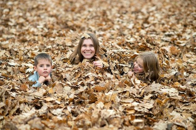 Madre con bambini in posa in foglie di autunno