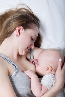 Madre con bambino carino sdraiato sul letto. allattamento al seno. concetto di famiglia amorevole felice vista dall'alto.