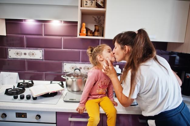 Madre con figlia che cucina in cucina, momenti felici per bambini. la mamma bacia il suo bambino.