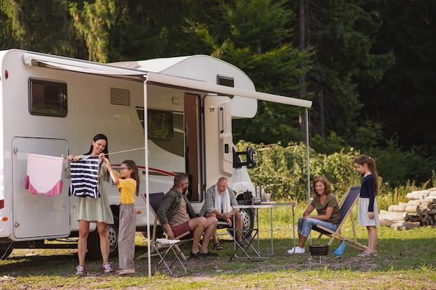 Una madre con la figlia che appende i vestiti in auto all'aperto in campeggio caravan vacanza in famiglia viaggio