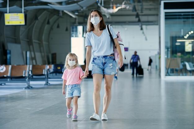 Madre con figlia mascherata in attesa del volo all'aeroporto donna con bambina dentro