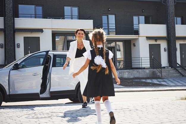 Madre con figlia in uniforme scolastica all'aperto vicino all'auto bianca.
