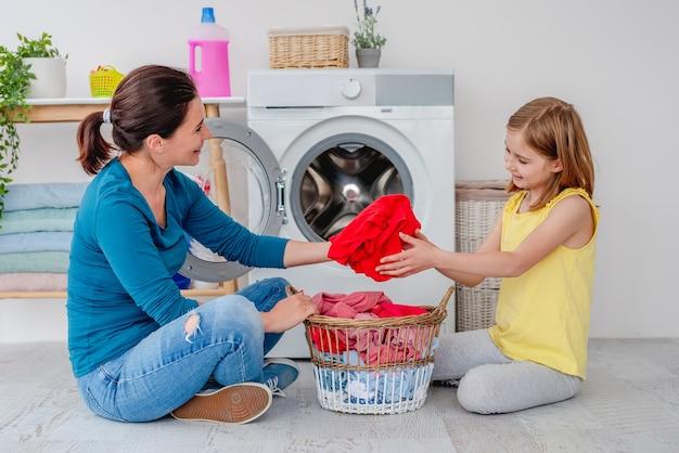 Madre con figlia che si siede sul pavimento vicino alla lavatrice con vestiti nel cestino in bagno luminoso