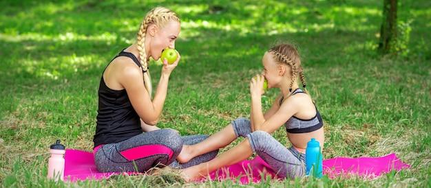 La madre con la figlia in abiti sportivi mangia le mele che si siedono su una stuoia nel parco estivo