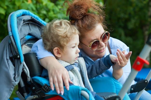 Madre con figlio disabile che cammina all'aperto con walker, attrezzature mediche per la mobilità.