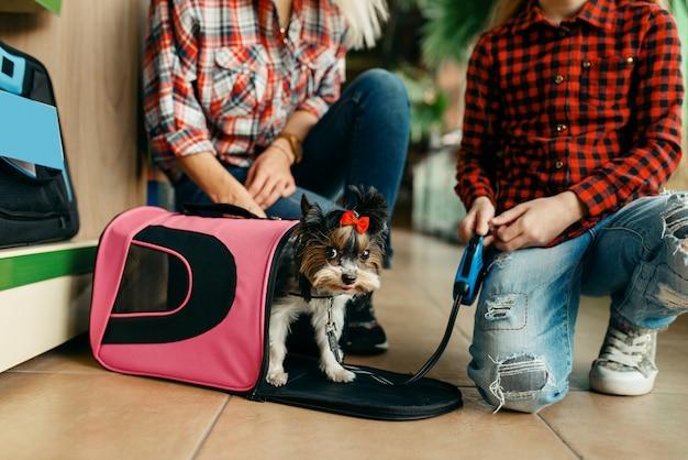 Madre con la ragazza che sceglie la borsa per il piccolo cucciolo nel negozio di animali.