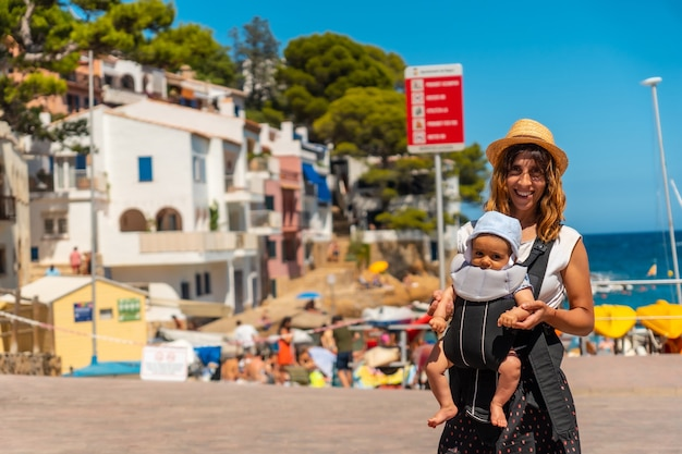 Una madre con il suo bambino sulla spiaggia di sa tuna sulla costa di begur in estate, girona sulla costa brava della catalogna nel mediterraneo
