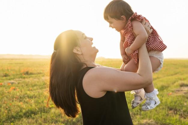 Madre con la figlia bambina in braccio nel campo di papaveri al tramonto
