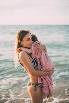 Madre con sua figlia in braccio sullo sfondo del mare di azov in crimea fresco