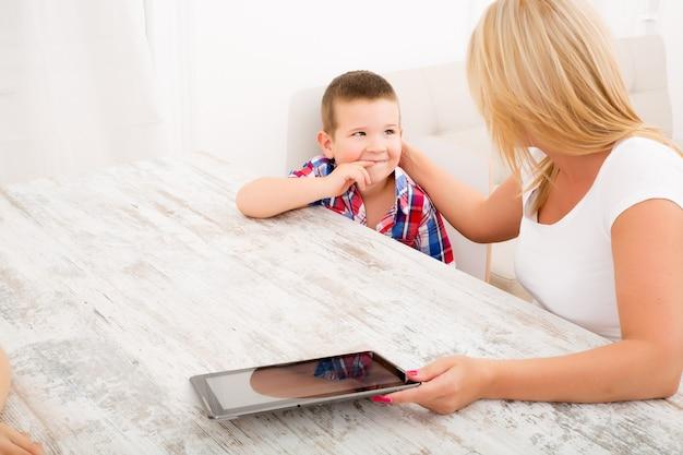 Una madre con i suoi figli utilizzando un tablet pc a casa.