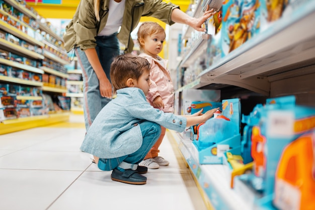 Madre con i suoi bambini piccoli allo scaffale nel negozio per bambini.