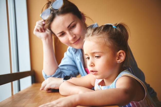 Madre con la sua piccola figlia seduta vicino alla finestra del caffè. in attesa dell'ordine