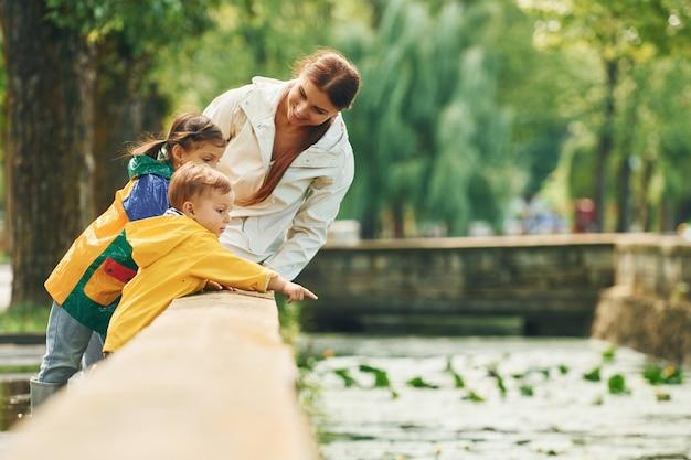 La madre con il figlio piccolo e la figlia fanno una passeggiata all'aperto nel parco dopo la pioggia.