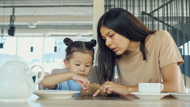 Madre con bambina al ristorante. la giovane donna asiatica bruna e la figlia piccola scelgono il menu seduti al tavolo del caffè in legno marrone vista ravvicinata