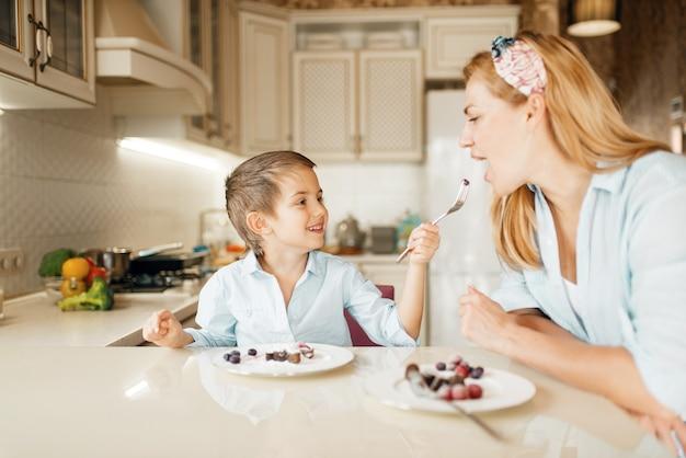 Madre con bambino degustazione dessert e divertirsi