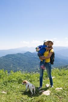 Madre con la figlia di una bambina in viaggio in montagna con il cane