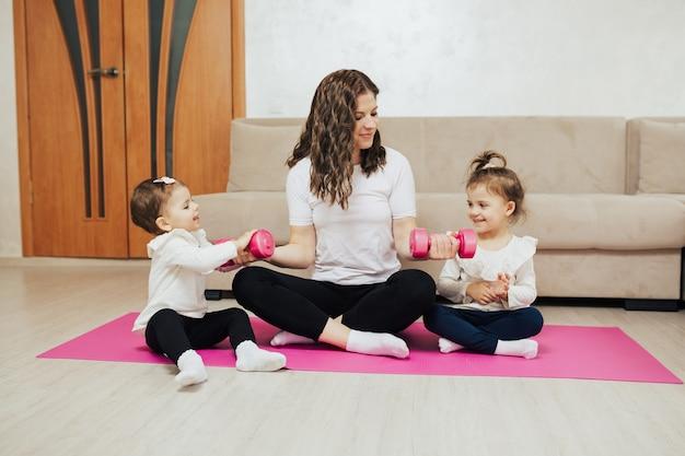 Madre con bambini piccoli sta facendo ginnastica ed esercizi di fitness con manubri