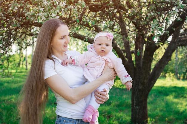 La madre con amore e tenerezza guarda il bambino. la mamma tiene la piccola figlia sulle mani. concetto di maternità genitorialità.