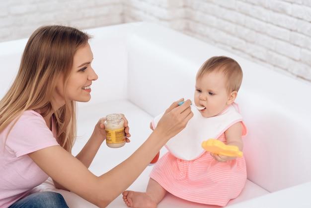 Madre con purea e cucchiaio che alimenta piccolo bambino.