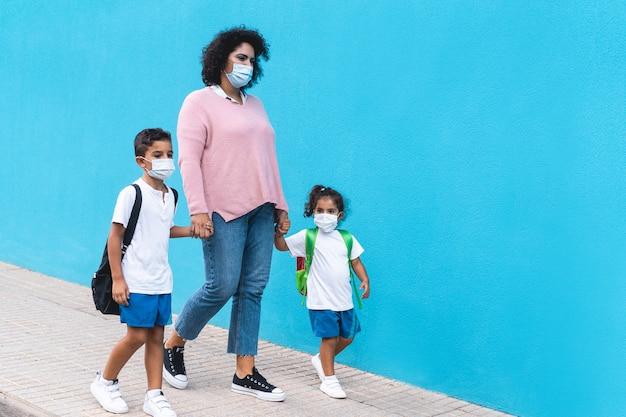 Madre con figlio e figlia che tornano a scuola indossando maschere per il viso - stile di vita e concetto di famiglia del coronavirus - focus principale sulla mamma