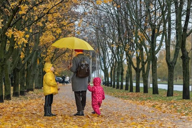 La madre con due bambini sta camminando nel parco con l'ombrello giallo sotto la pioggia. parco d'autunno, foglie cadute. famiglia felice.