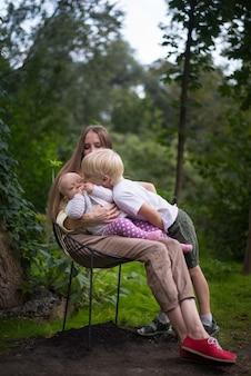 Madre con due bambini seduti su una sedia sullo sfondo della natura. cornice verticale.