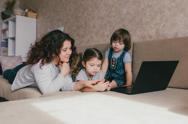 Una madre con due giovani figlie è sdraiata sul divano e guarda il telefono. mamma e bambini in vacanza in comune