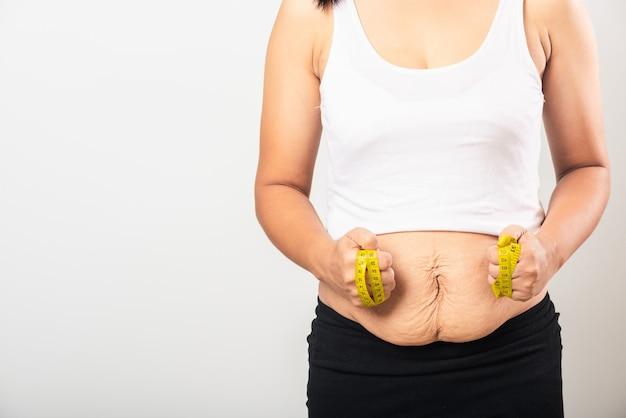 La donna madre usa la sezione di misurazione della smagliatura della vita nell'addome inferiore grasso della pelle dopo il parto