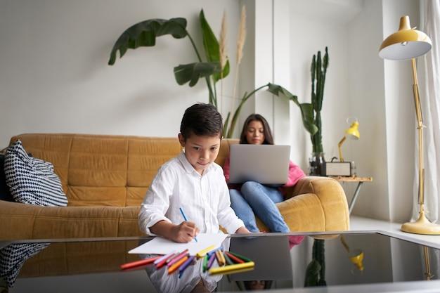 La madre lavora al laptop mentre suo figlio dipinge immagini sullo stile di vita del tavolo del soggiorno con...