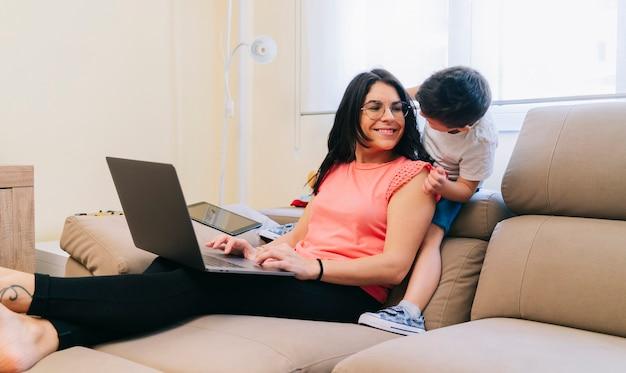 Una madre lavora sul divano di casa con il computer con il figlio che gioca con lei