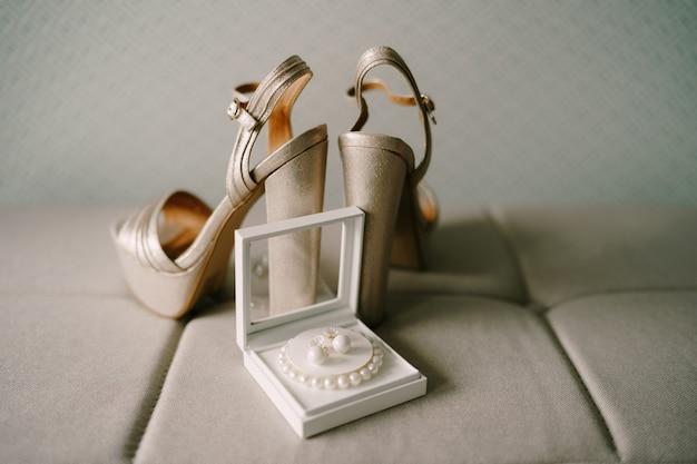 Sandali con plateau in madreperla con tacco alto e una scatola con un braccialetto di perline bianche e orecchini su a