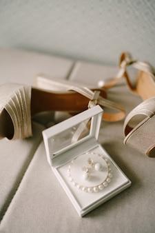 Sandali da donna in madreperla e una scatola con un braccialetto di perline bianche e orecchini