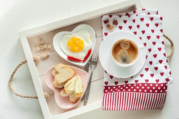 Colazione per la festa della mamma. vassoio c'è una tazza di caffè due piatti di uova strapazzate e pane a forma di cuore e la scritta ti amo mamma vista dall'alto
