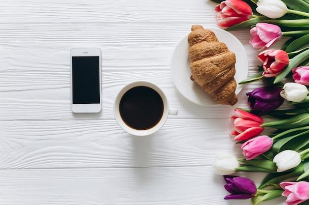 Concetto di giorno della madre bouquet di tulipani, caffè, croissant e smartphone.