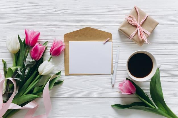 Concetto di giorno della madre bouquet di tulipani, caffè, carta con copia spazio e regalo.